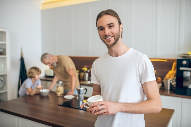 Morning at home. young man in white tshirt standing in the kitchen and smiling