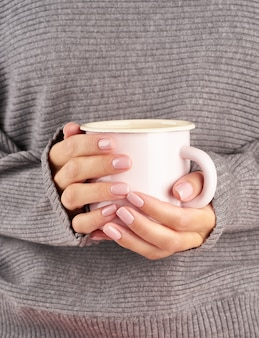 Morning hot coffee at work on a cold autumn morning, hands holding a mug with a drink, gray sweater