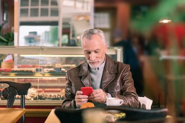 パン屋の朝。仕事の前にパン屋で朝を過ごして安心しているひげを生やした白髪のビジネスマン