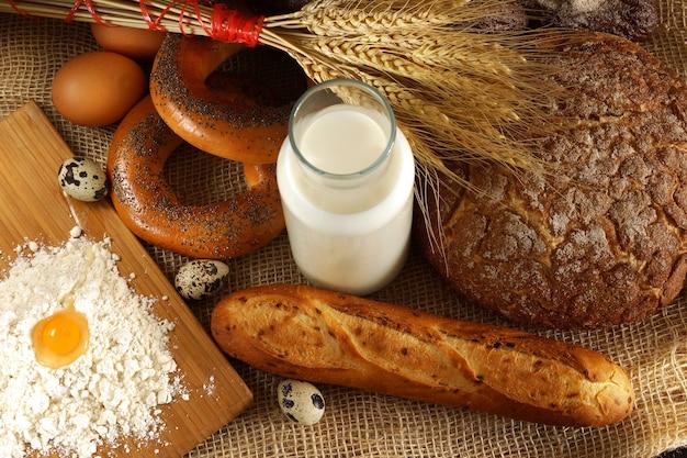 빵집의 아침, 테이블에 여러 종류의 신선한 빵, 밀가루 및 계란과 우유.