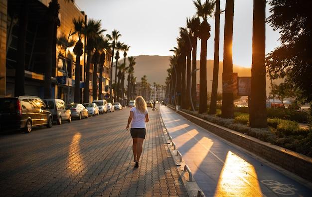 Утренняя пробежка молодой женщины по дороге в городе мармарис, турция