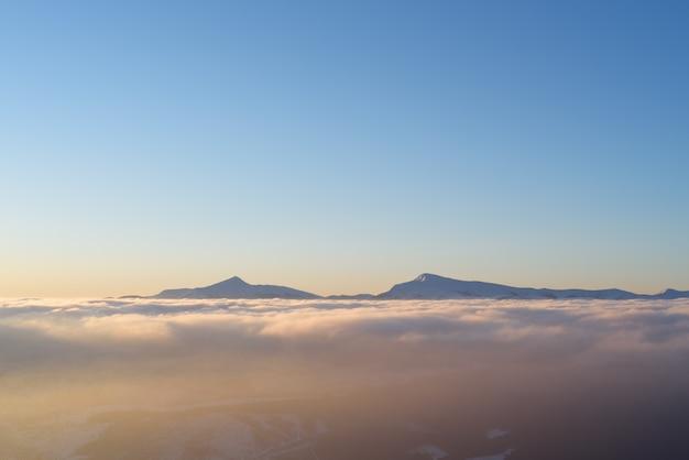 Утренний пейзаж зимой. горные вершины в облаках. карпаты, украина, европа