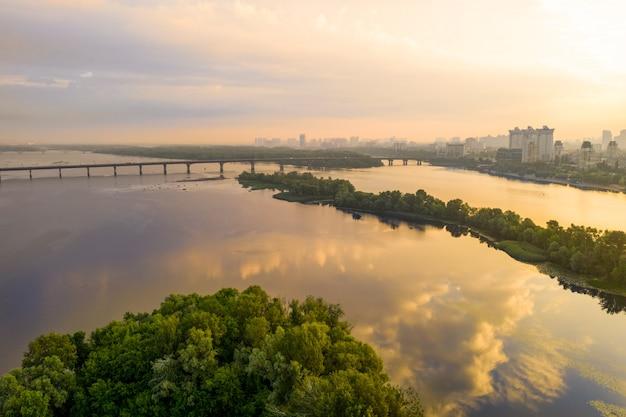 Утренний пейзаж с речной поверхностью, остров с деревьями, мост и город на горизонте