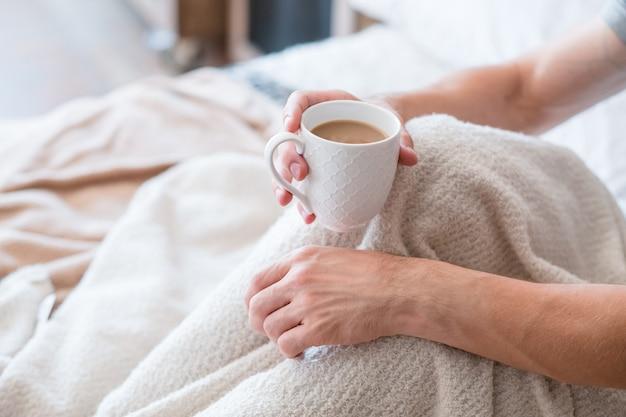 Утренний латте. просыпайся, пей. человек с чашкой в постели. отдых и досуг. уют в спальне.