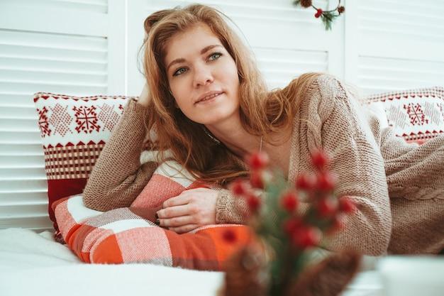 Утро, досуг, рождество, зима и люди концепции - счастливая молодая женщина в постели в домашней спальне