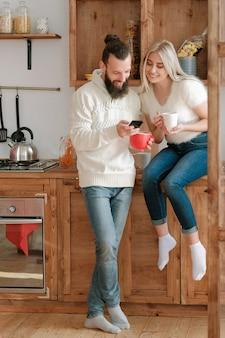 아침 여가. 부부는 부엌에서 커피를 마시고, 스마트 폰을 사용하여 인터넷에서 재미있는 뉴스를 읽고 함께 시간을 즐기고 있습니다.
