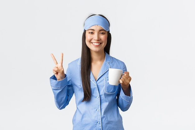 朝のライフスタイル、朝食、人々の概念。青いパジャマと眠っているマスクで陽気な笑顔のアジアの女の子、目を覚ます、コーヒーを飲み、かわいいピースサイン、白い壁を示します。