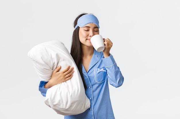 朝のライフスタイル、朝食、人々のコンセプト。パジャマとスリーピングマスクで美しいアジアの女の子を笑顔、枕を抱き締め、ベッドでコーヒーを飲み、テレビを見て、週末のホームレジャー。