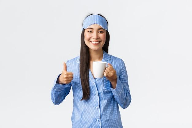 朝のライフスタイル、朝食、人々のコンセプト。眠っているマスクとパジャマを着た明るい笑顔のかわいいアジアの女の子は、目覚めた後にコーヒーを飲んでいるように親指を立てて、エネルギーに満ちていると感じています。
