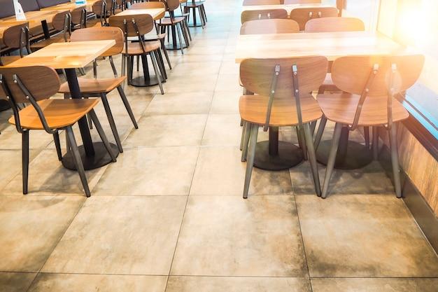 Утренний свет сквозь ряды пустого стола и стульев в кафе-ресторане