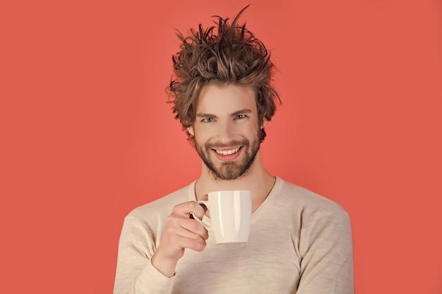乱れた髪の朝の男はお茶を飲む