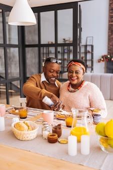 朝の食事。彼らのおいしい朝食を楽しみながら笑顔で喜んでポジティブなカップル