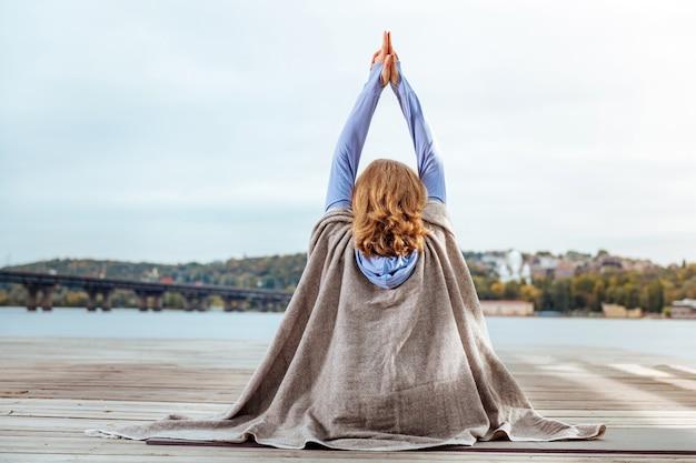 朝の瞑想。川の近くで朝の瞑想をしている穏やかで刺激を受けた女性