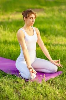 Утренняя медитация женщина на коврике для йоги, чтобы расслабиться на открытом воздухе
