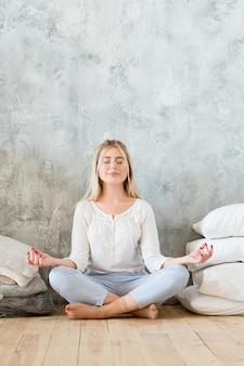 朝の瞑想。ライフスタイルのコンセプト。ムドラジェスチャーで足を組んで床に座っている若い女性。