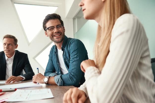 朝の会議。現代のオフィスに座って何かを話し合い、笑顔でビジネスチーム。ブレーンストーミング。チームワーク