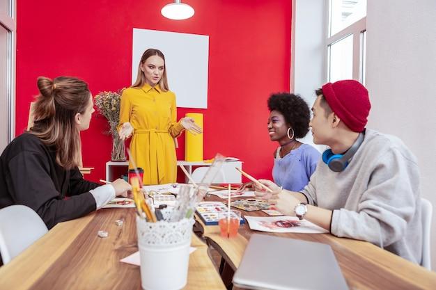 朝の会議。新しいプロジェクトについて話し合う伝統的な朝の会議を持っているスタイリッシュなファッションデザイナー
