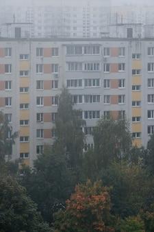 Утренний туман над панельными домами ранней осенью.