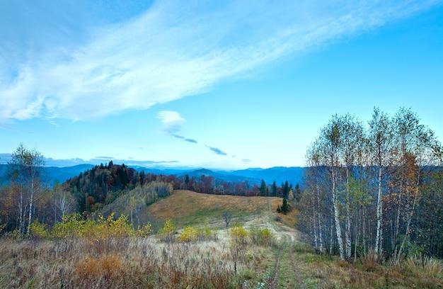 山腹に田舎道のある朝の霧深い秋の山の風景(カルパティア山脈、ウクライナ)