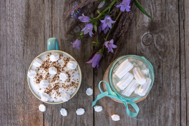 Morning mocha with marshmallows on a wooden table with flowers.