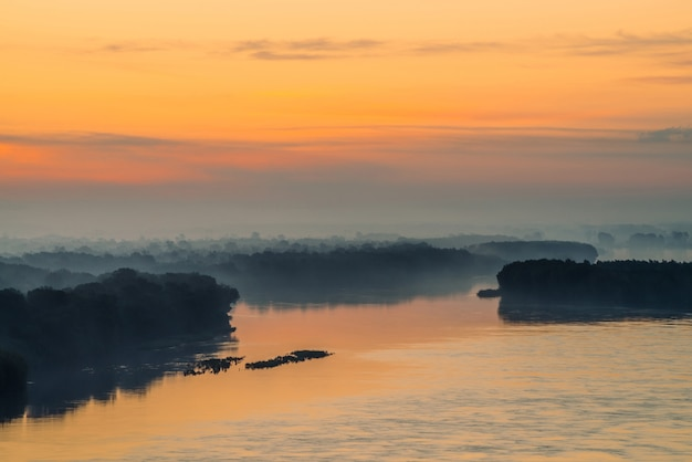 Утренняя мистическая дымка над широкой долиной реки. золотое сияние от рассвета в небе. берег реки с лесом под туманом.