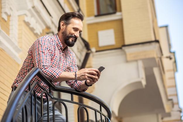 朝のニュース。ベランダに立っている間彼のスマートフォンを使用して陽気なハンサムな男