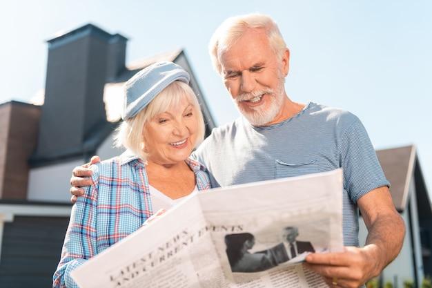 Утренняя газета. счастливая пара на пенсии, вместе читая утреннюю газету возле своего дома