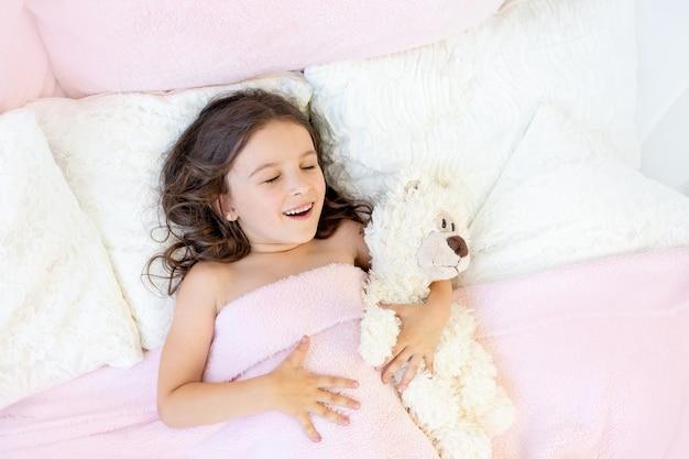 Утро маленькой девочки 5-6 лет, девочка зевает в постели с мишкой тедди