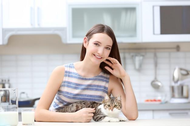 キッチンで美しい若い女性と猫の朝