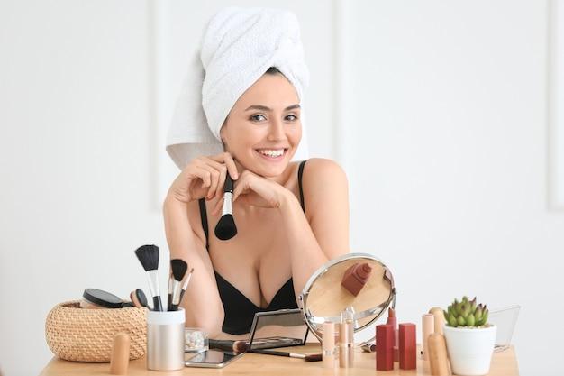 Утро красивой молодой женщины, применяющей макияж дома
