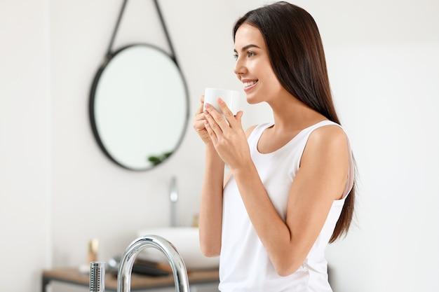 浴室でコーヒーを飲む美しい若い女性の朝
