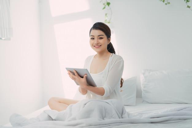 Утро красивой молодой женщины с планшетным компьютером в спальне