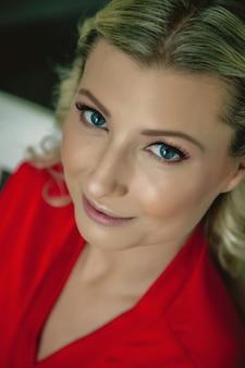 花嫁の朝。笑ってホテルの部屋で楽しんで座っている赤いローブで真っ白な笑顔で幸せな美しい