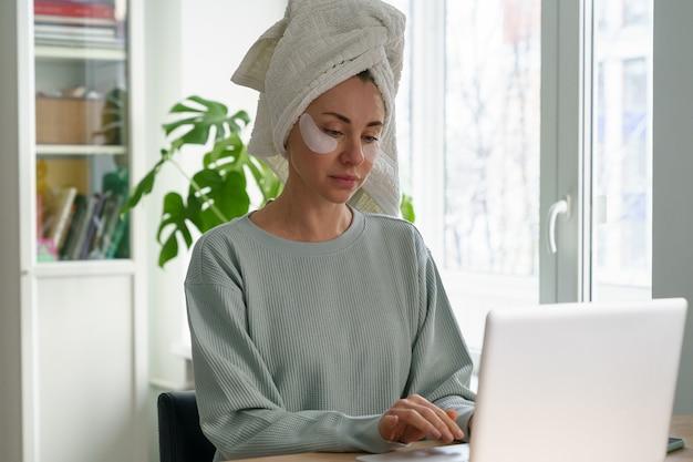 頭にタオルとパッチでホームオフィスの女性から働く実業家の朝はラップトップを使用します