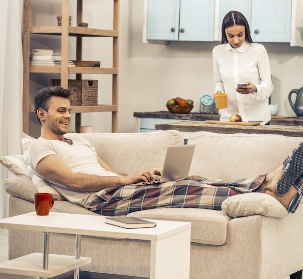 幸せな朝のカップルが自宅で仕事