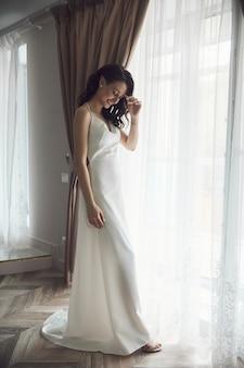 신부의 아침. 아름다운 여인이 결혼식, 자연스러운 메이크업 및 세련된 헤어 스타일을 준비하고 있습니다. 흰색 실내복과 웨딩 드레스