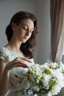 Утро невесты. красивая женщина готовится к свадьбе, естественный макияж и шикарная прическа. белый пеньюар и свадебное платье