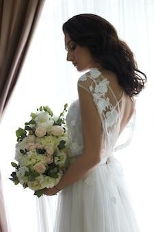 花嫁の朝。美しい女性が結婚式、ナチュラルメイク、シックなヘアスタイルの準備をしています。白いペニョワールとウェディングドレス