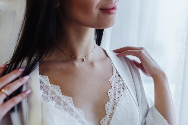 花嫁の朝。白いローブを着た女の子が窓の近くに立っています