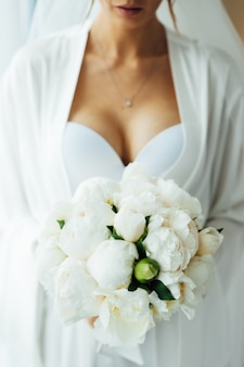 ホテルの部屋で花嫁の朝。手の中の花束のわずかにぼやけた画像。