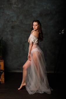 花嫁の朝。白いレースの下着でポーズをとってセクシーな女の子。白い下着の美しい若い女性の肖像画。白いリネンとペニョワールランジェリーの魅惑的な女性。