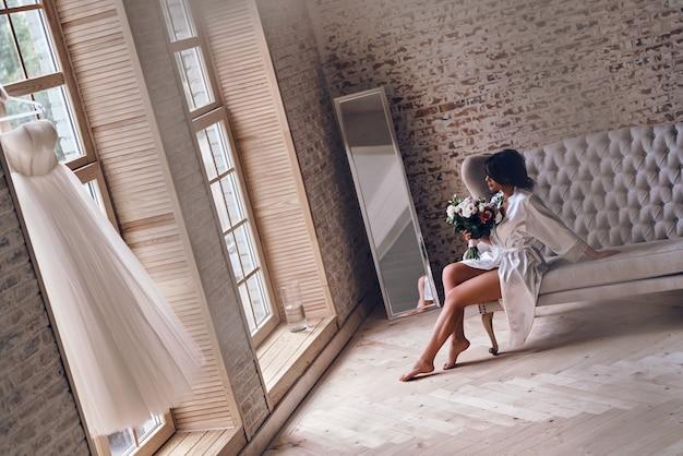 最も重要な日の朝。ソファに座っている間花束を保持している絹のバスローブで美しい若い女性
