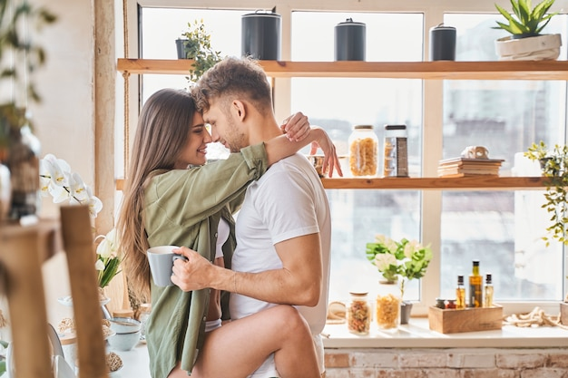 Morning passion. handsome bearded man standing in semi position and enjoying close contact with his girlfriend