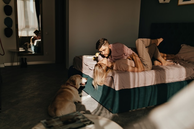 Morning photo of men and women admiring each other, lying on bed with dog on floor. couple enjoying weekend in their apartment.
