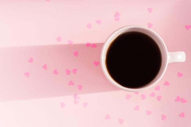 흩어져 종이 마음으로 분홍색 배경에 차 아침 핑크 컵. 사랑과 관리 개념입니다. 텍스트를위한 공간 복사
