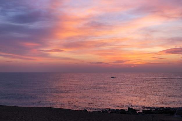 朝のピンクの空が海に映る日の出の間に航海する小さな孤独な漁師のボートのシルエット海の海岸の美しい海に沈む夕日