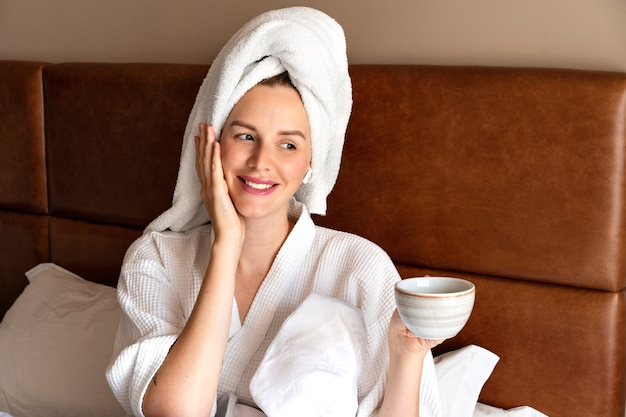 Утренний портрет красивой женщины, расслабляющейся в постели после душа в халате и полотенце на голове, пьющей вкусный чай