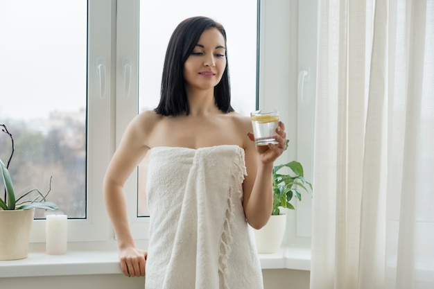 Morning portrait of young beautiful woman in bath towel with glass of water with lemon near the window.