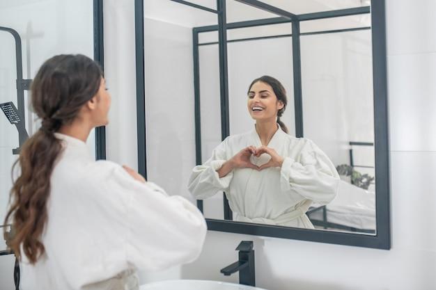 朝の手順。バスルームにバスローブを着た若い女性の写真