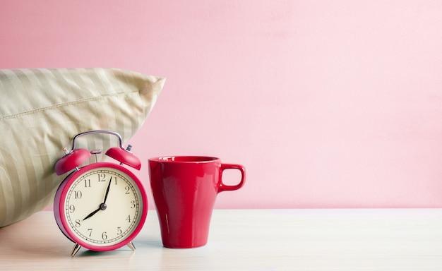 ピンクの壁の背景にベッドサイドテーブルの枕の近くの朝の赤い目覚まし時計と赤いマグカップ